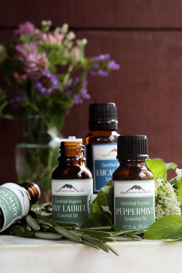 Rosemary, Bay Laure, Eucalyptus, and Peppermint Essential oils surrounded by fresh botanicals.