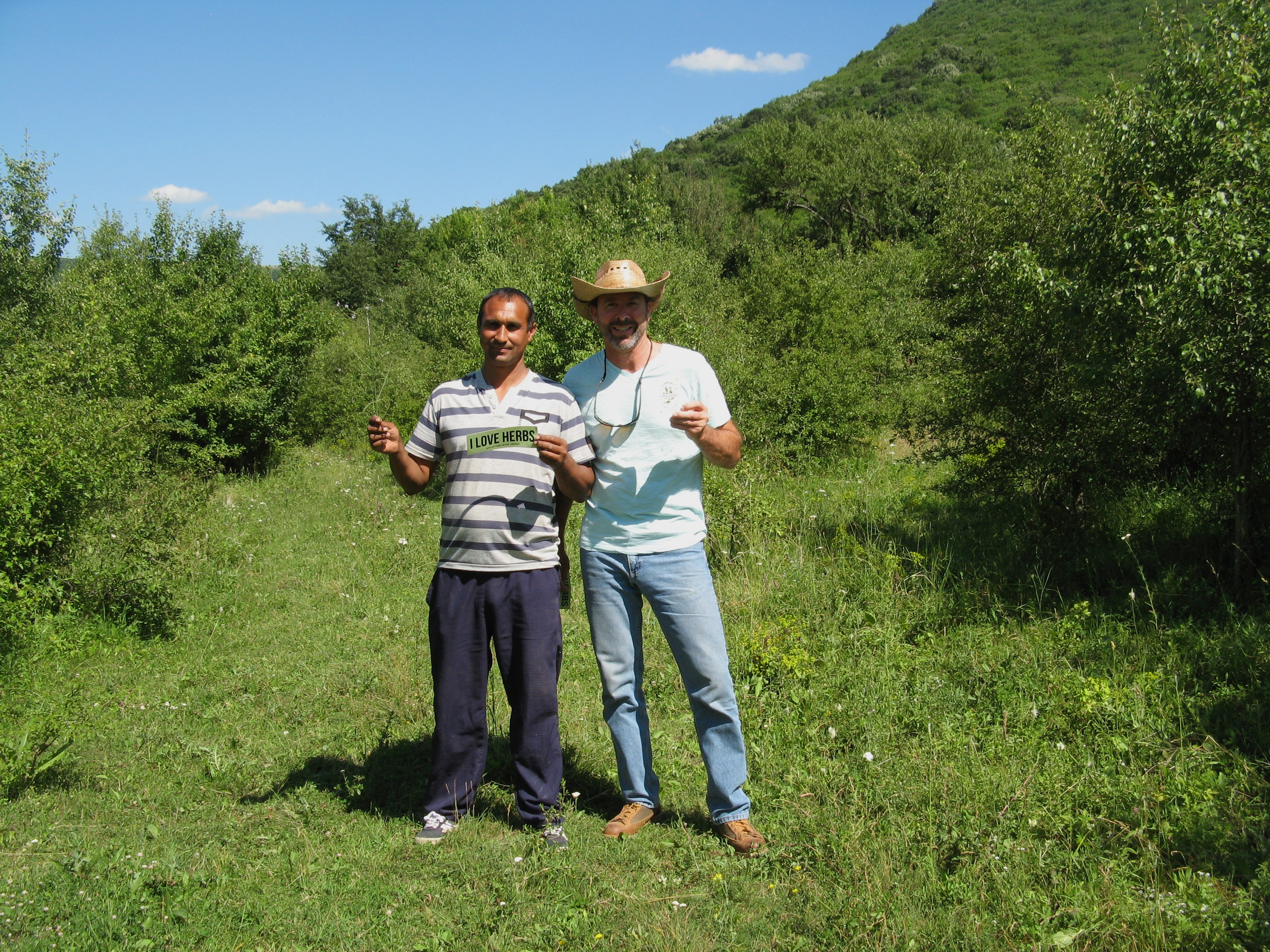 Mountain Rose Herbs procurement officer standing with farmer holding I Love Herbs bumper sticker in a field in Bulgaria
