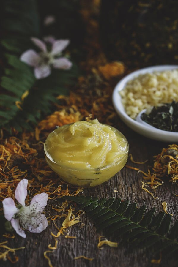 Bowl of natural herbal diaper rash ointment surrounded by botanical ingredients.