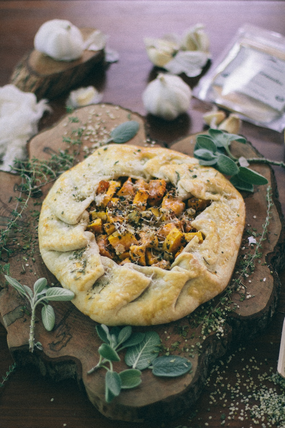 aerial view of savory squash galette on counter with dried and fresh herbs and spices