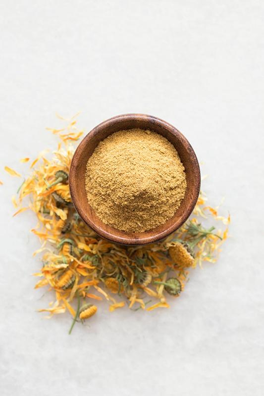 Terra cotta bowl full of organic calendula powder surrounded by calendula flowers