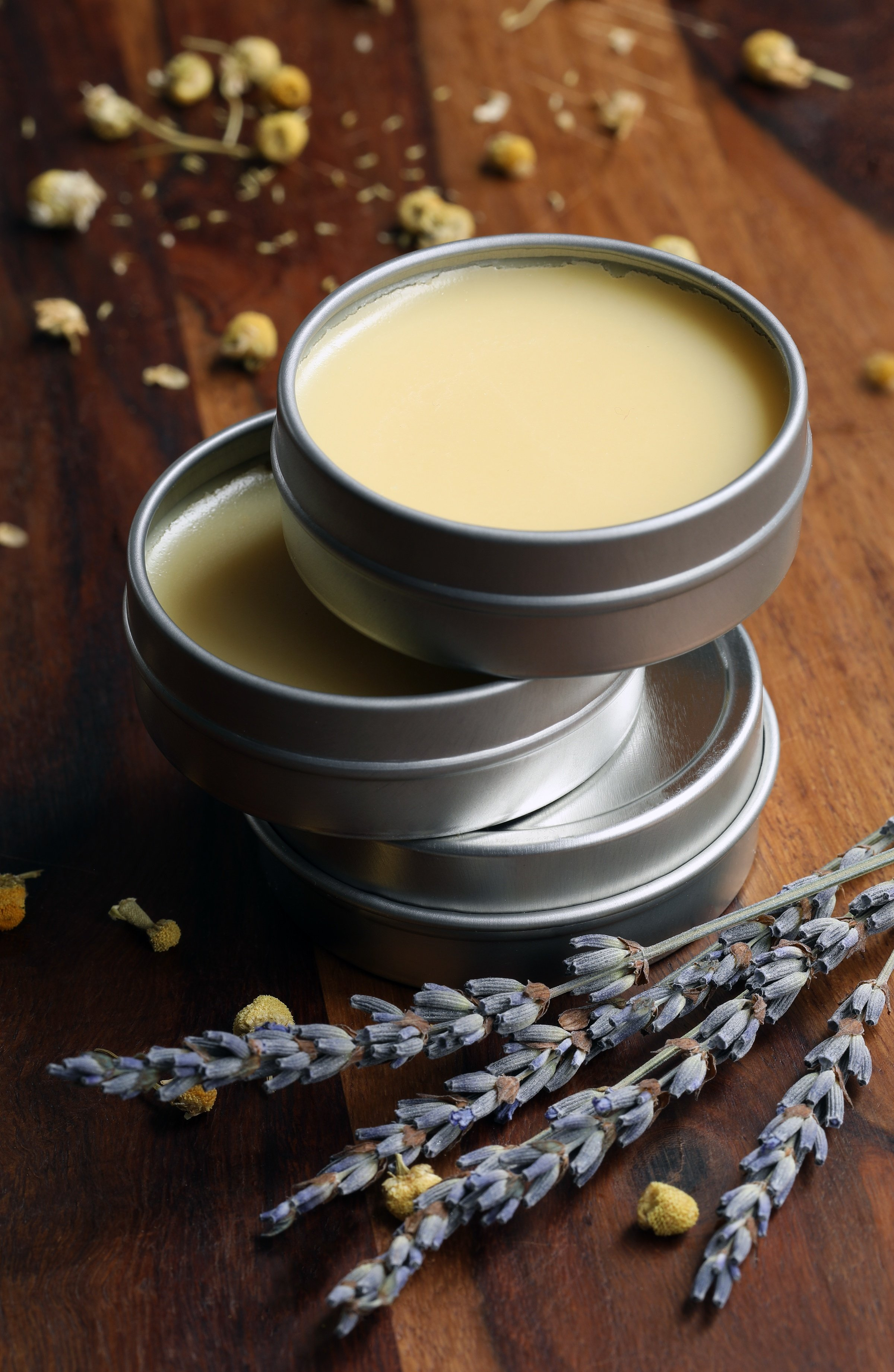 stacked tins of calendula vegan salve on wooden surface with dried herbs