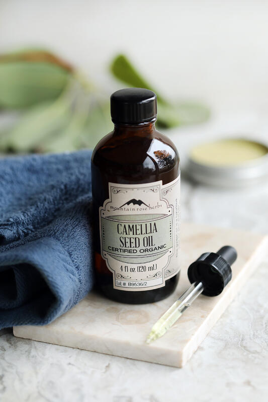 Bottle of Camellia Seed Oil displayed with a dropper, bright green plant and a crisp blue towel.