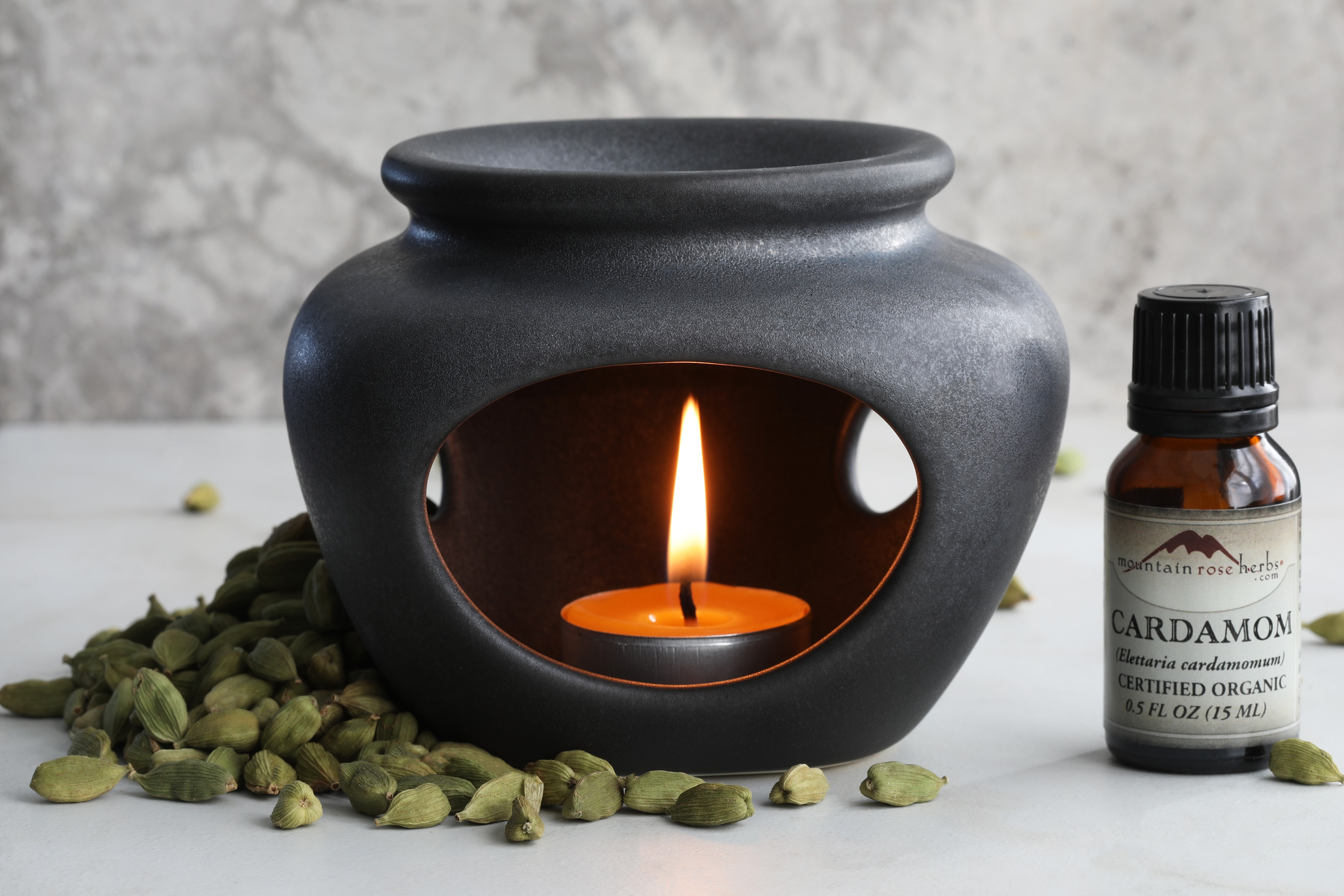 Tea light candle ceramic diffuser with lit candle and cardamom essential oil sitting next to cardamom pods