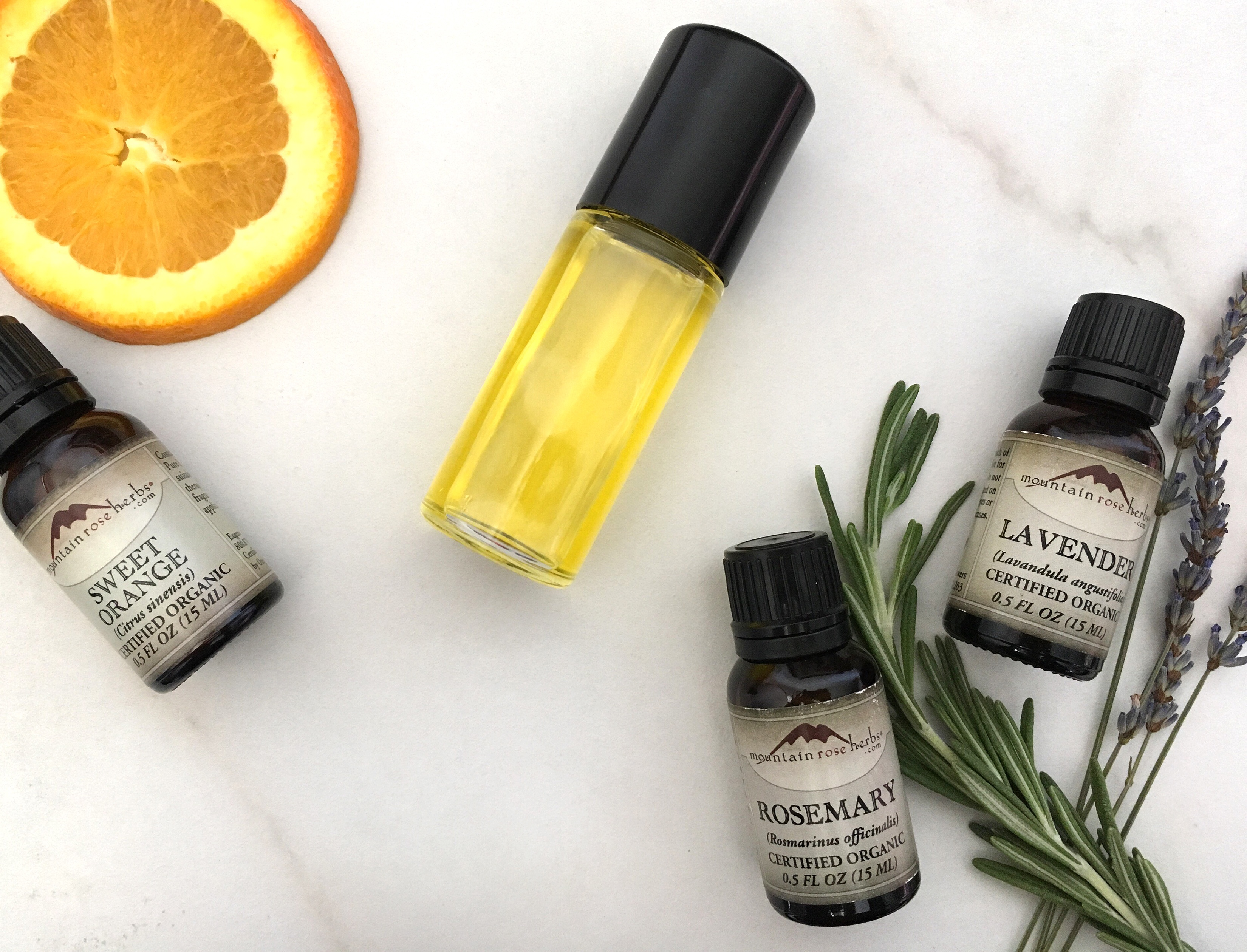 Roll top bottle filled with DIY aroma blend sitting on counter with sweet orange essential oil and lavender & rosemary essential oils