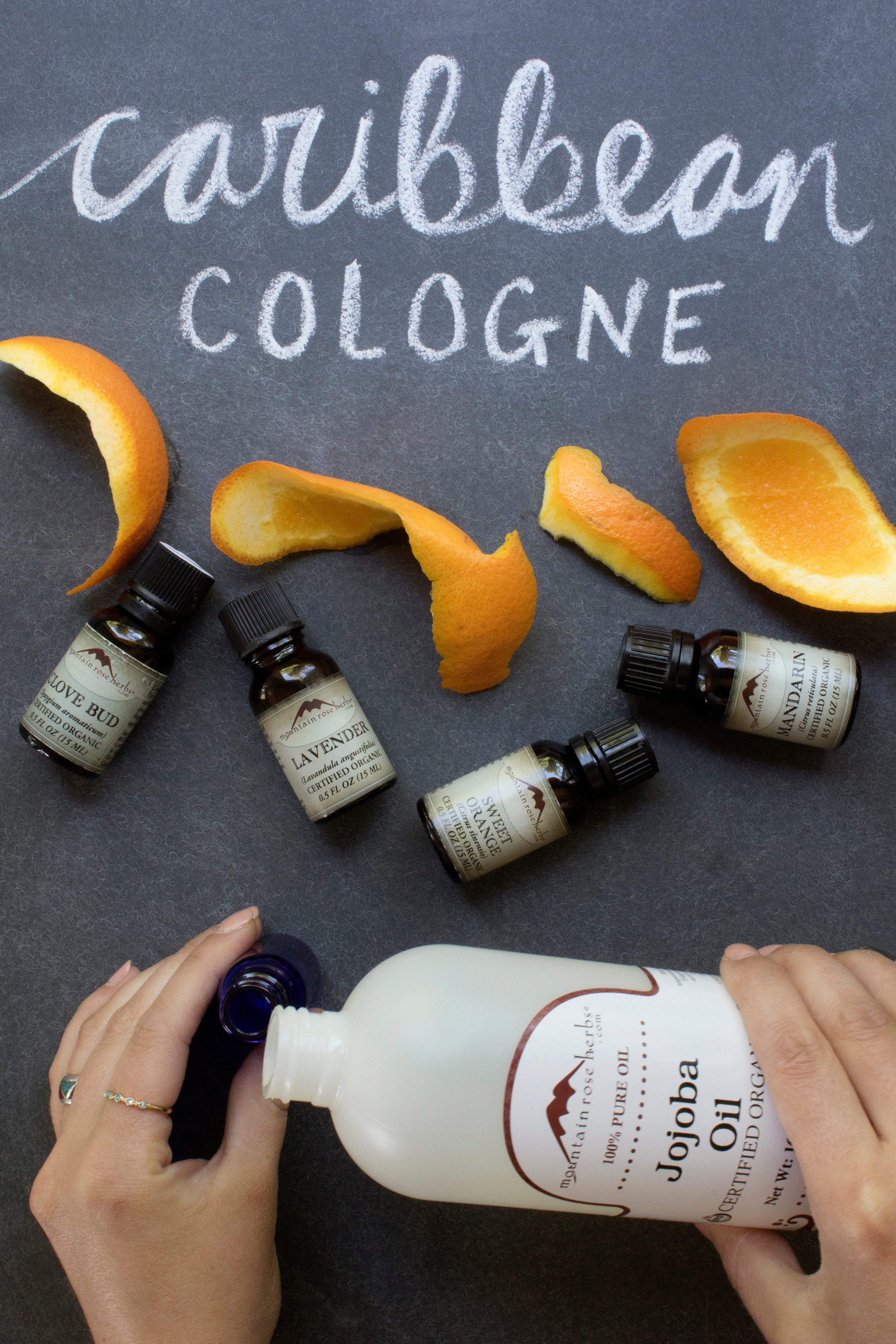 Hands pouring jojoba oil into glass bottle with citrus peels Caribbean Cologne essential oil fragrance recipe