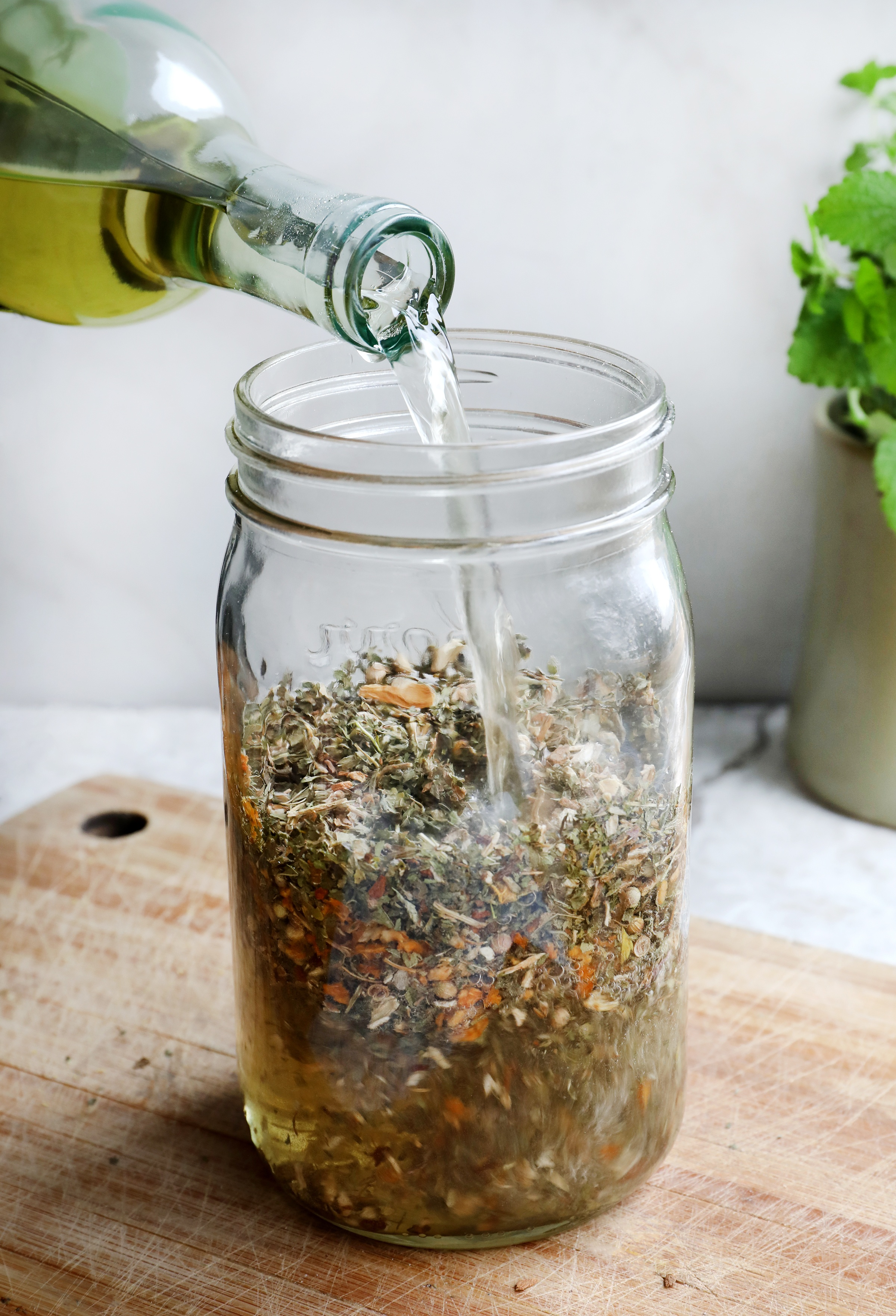 Pouring wine into a canning jar filled with dried herbs to make Carmelite water with lemon balm
