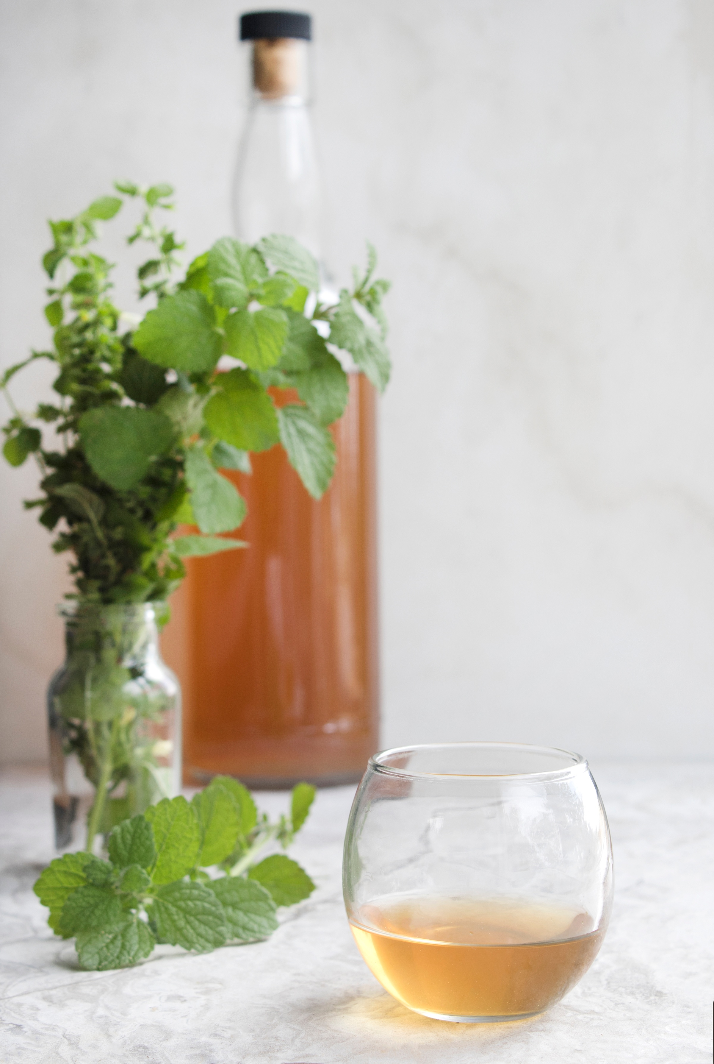 Clear globe glass holding Carmelite water near fresh lemon balm with bottle of amber liquid behind