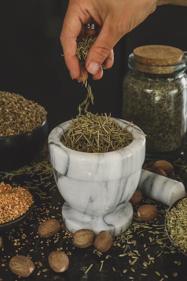 Hand dropping rosemary leaves into mortar and pestle.