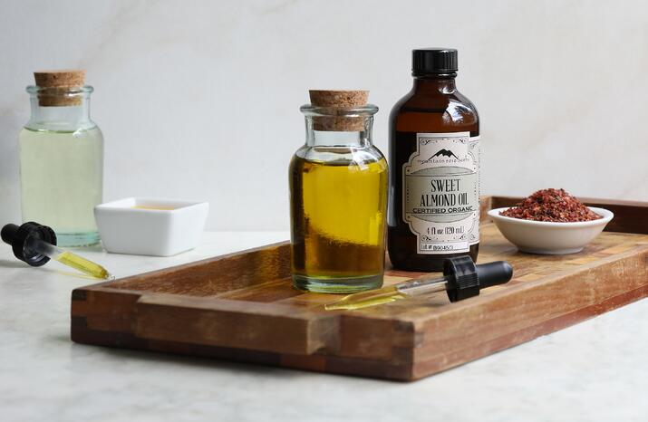 4 oz. bottle of sweet almond oil with glass bottle of oil on stray