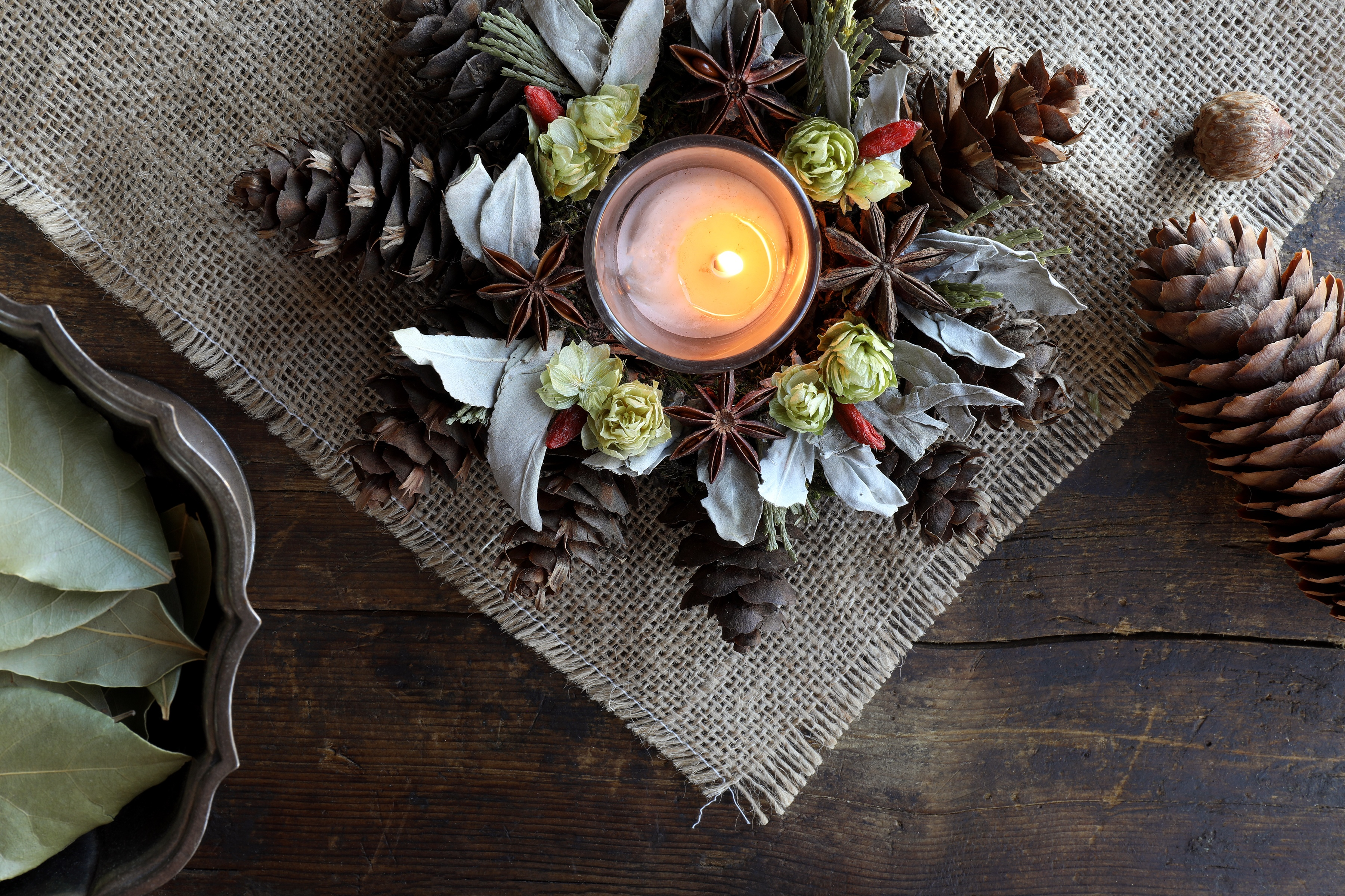 Center piece with holiday foliage decor and candle burning in middle , displayed on rustic wooden table and burlap