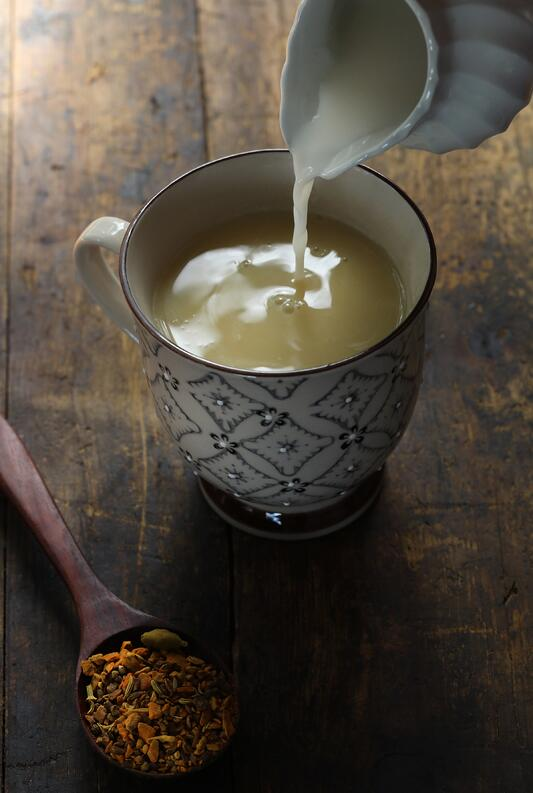 Pitcher with cream pouring into mug filled with turmeric chai
