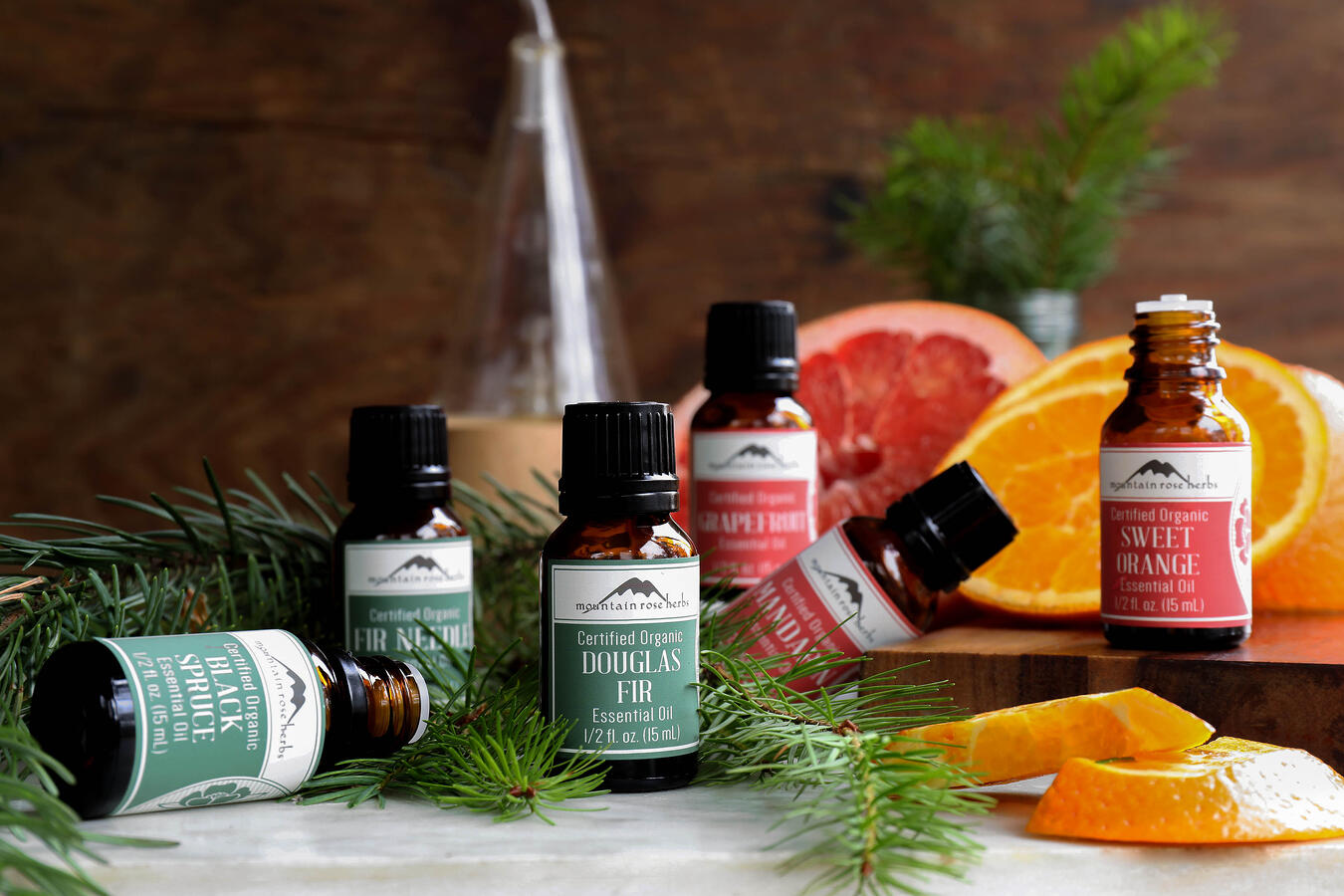 Black Spruce, Fir Needle, Douglas Fir, Grapefruit, Mandarin, and Sweet Orange essential oils surrounded by fir boughs and citrus.