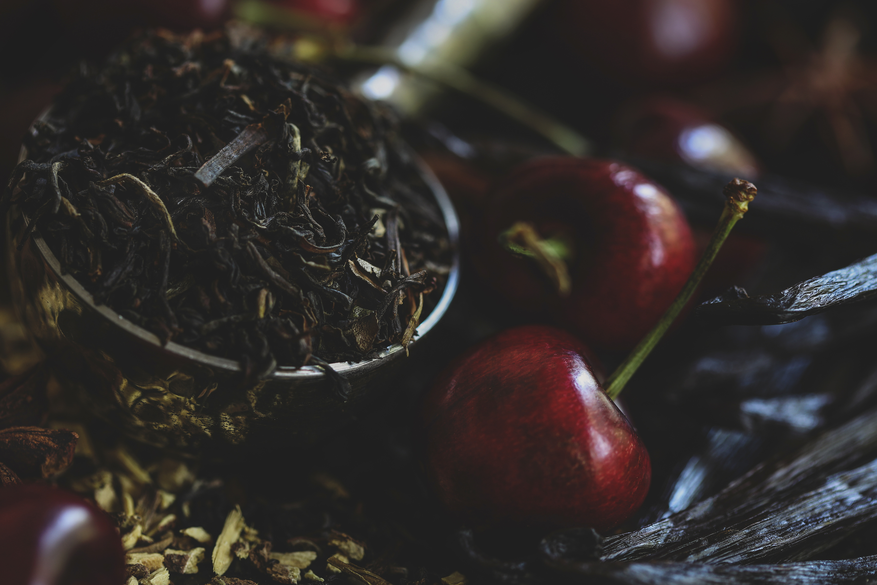 Fresh cherries surrounded by tea leaves and vanilla beans