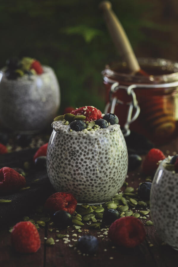 Glass cup with colorful chia putting and fresh berries.
