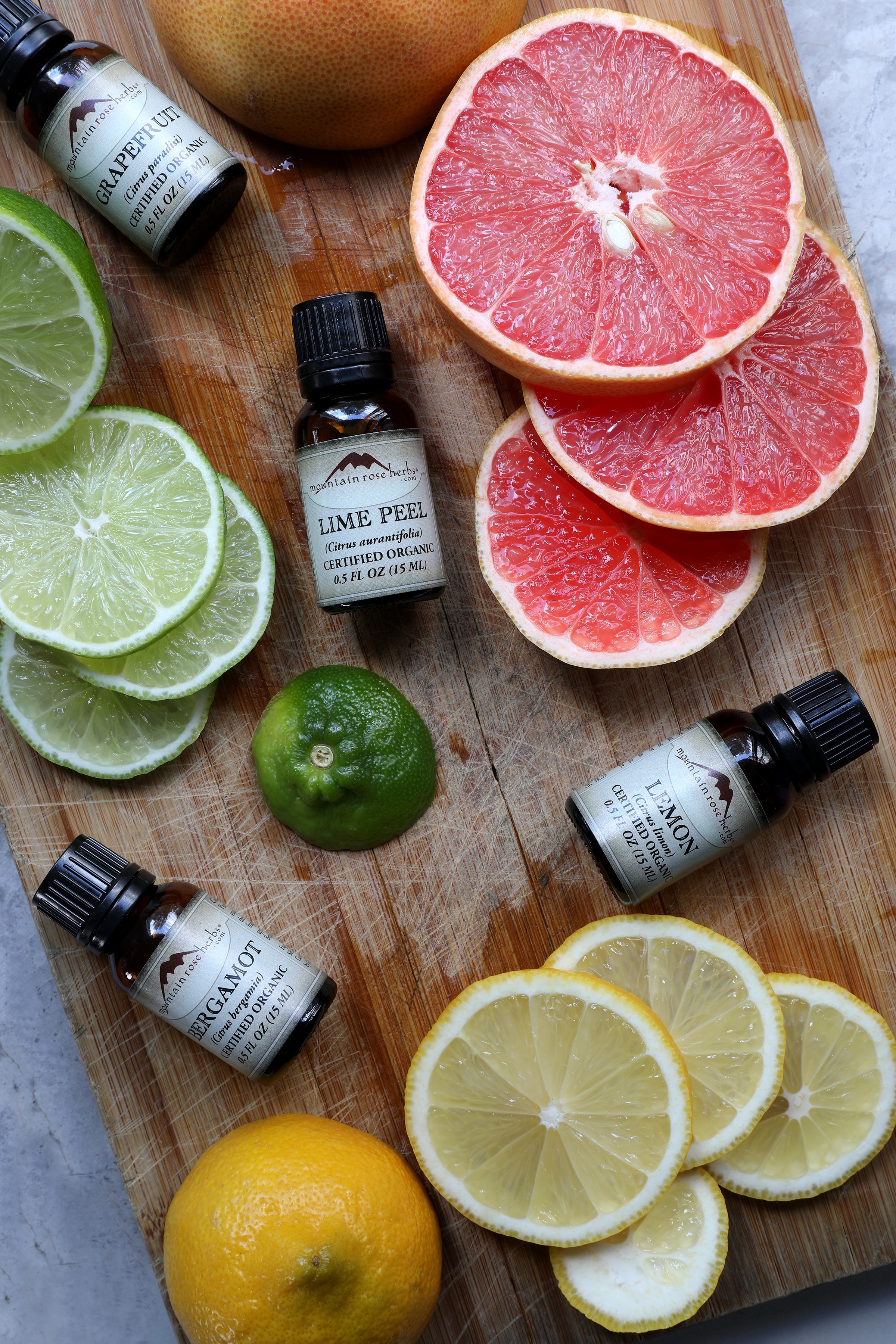 Lime peel essential oil, bergamot essential oil, lemon essential oil, and grapefruit essential oil on wooden chopping board with fresh fruit