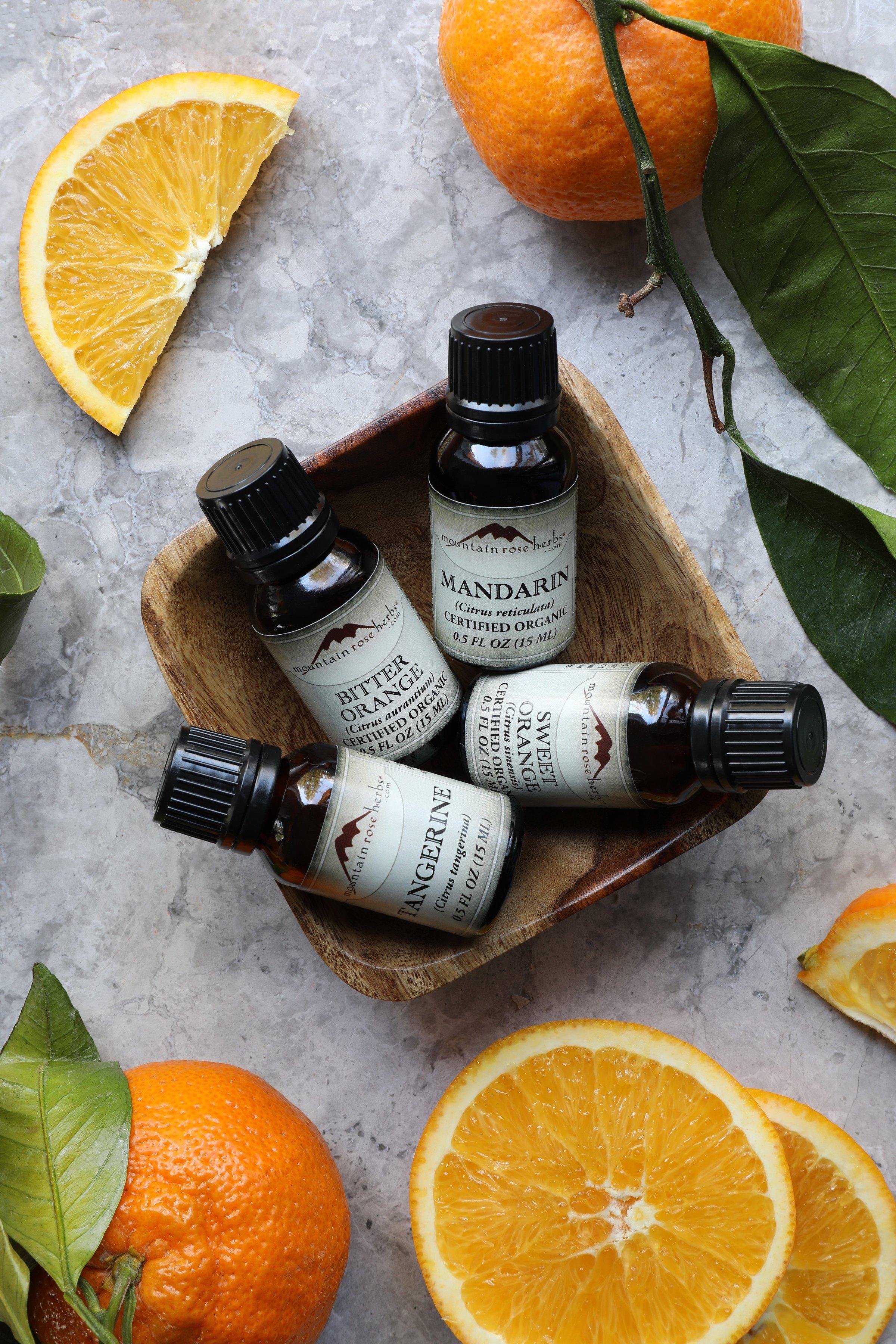 Mandarin essential oil, Sweet Orange essential oil, Bitter orange essential oil, and tangerine essential oil in a wooden bowl