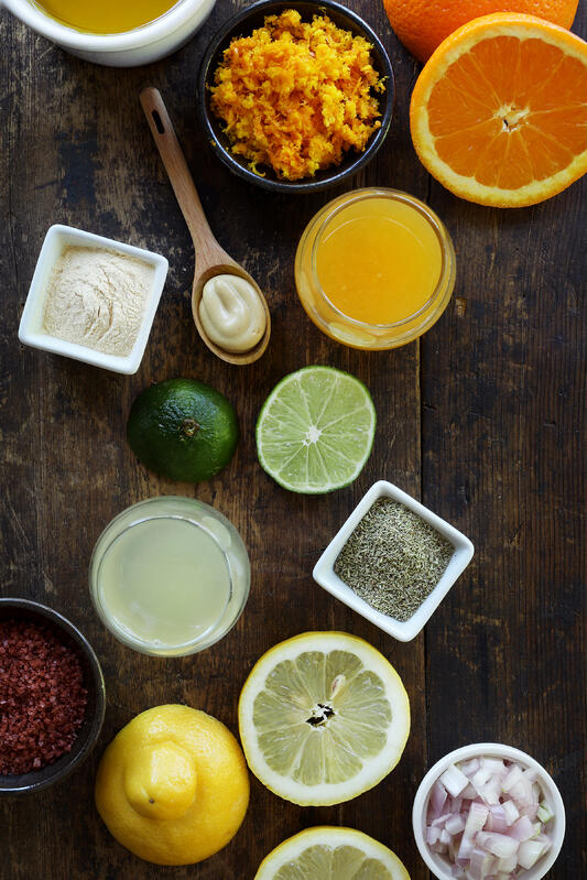 Ingredients for a citrus dressing are arranged on a rustic wooden tabletop. Ingredients include fresh lemon and orange, minced shallot, lime, vinegar, salt and orange rind.