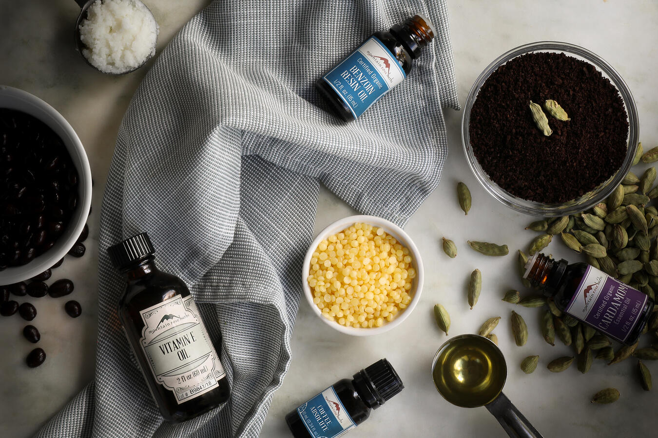 Ingredients to make uplifting coffee cardamom lip balm laid out on a table, including coffee beans, cardamom pods, vitamin e oil, essential oils and beeswax pastilles.