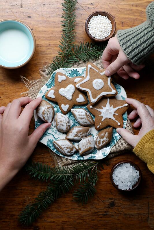 Hands picking up cookies off or a platter in a warm holiday setting.