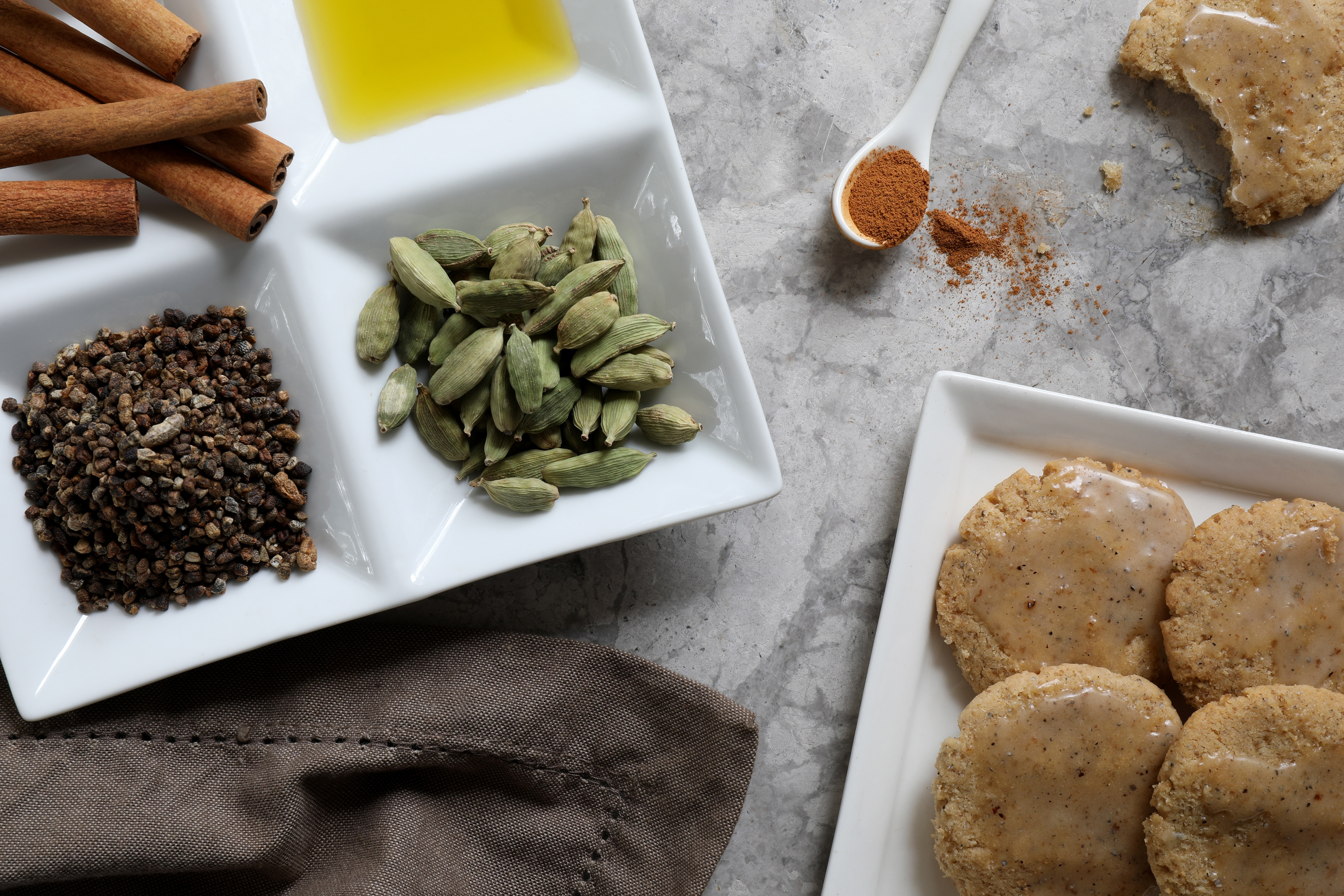 Ingredients for cardamom cookies on counter, plate of cardamom pods, cinnamon sticks, almond  oil