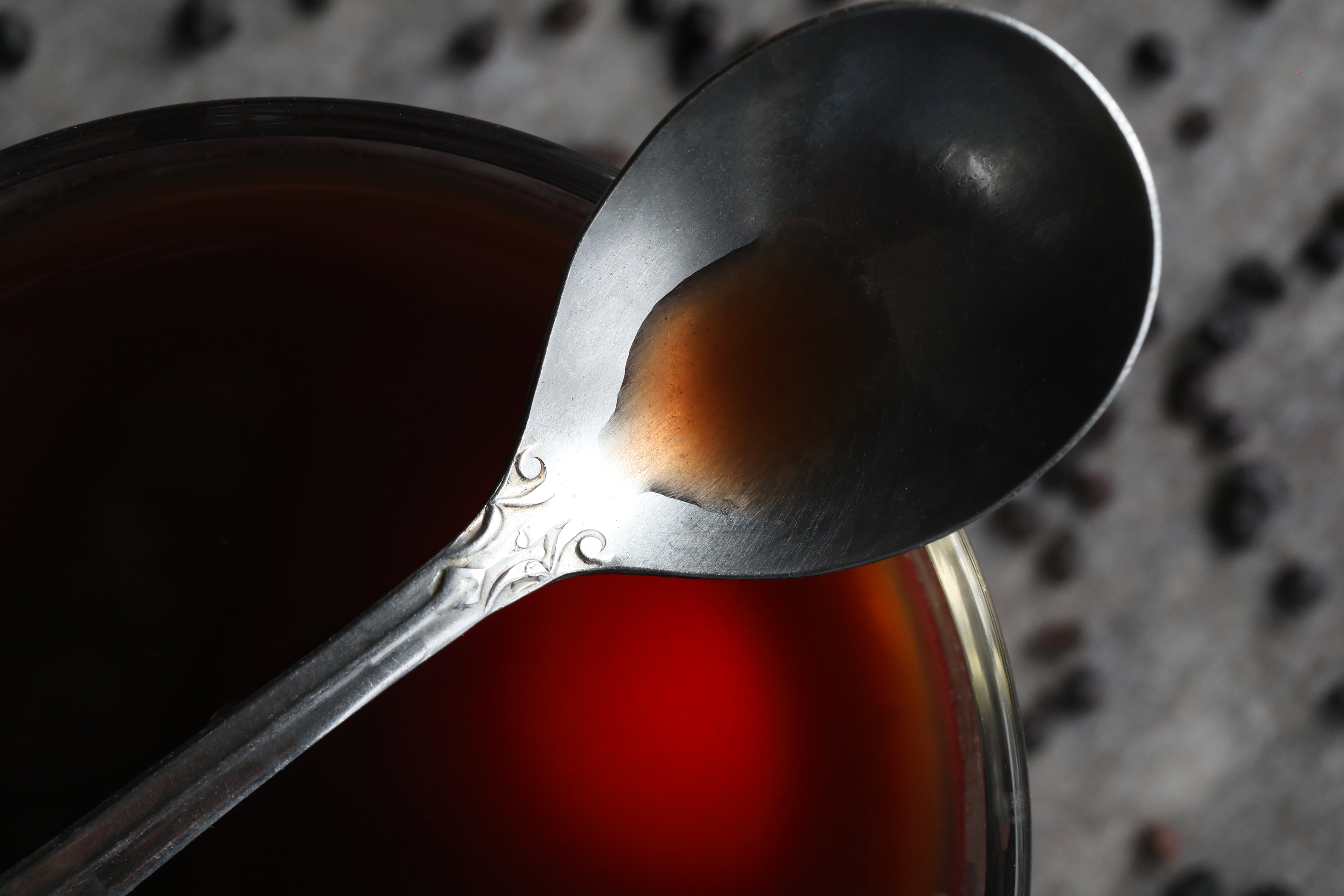Metal spoon with small amount of deep red syrup.