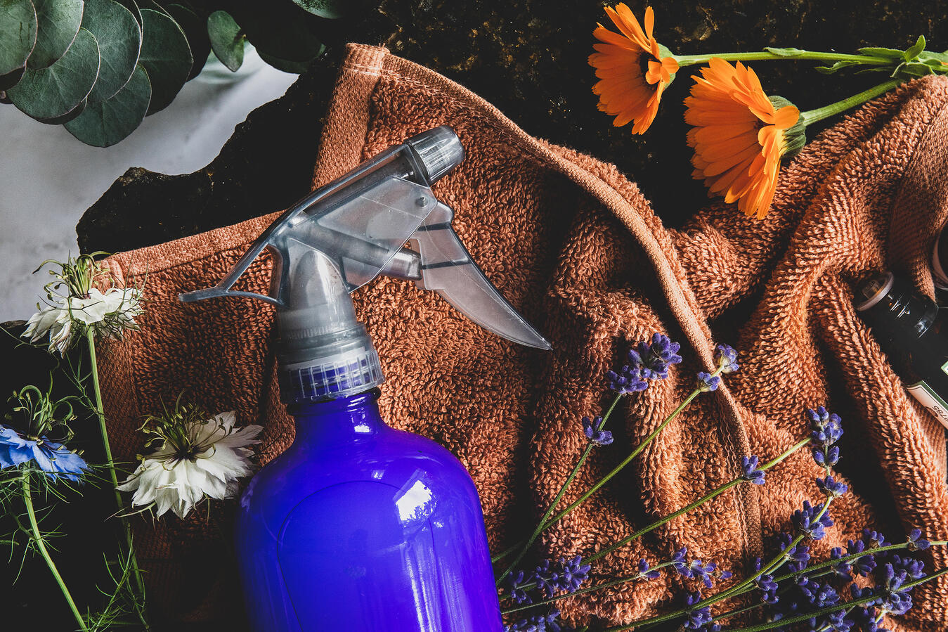 Spray bottle on a cloth with flowres and essential oils .