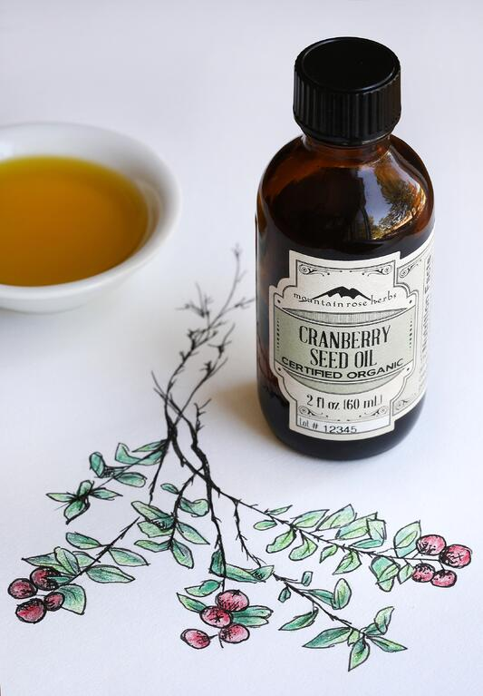 Bottle of organic cranberry seed oil with hand drawing of the cranberry plant and a bowl of oil in backround