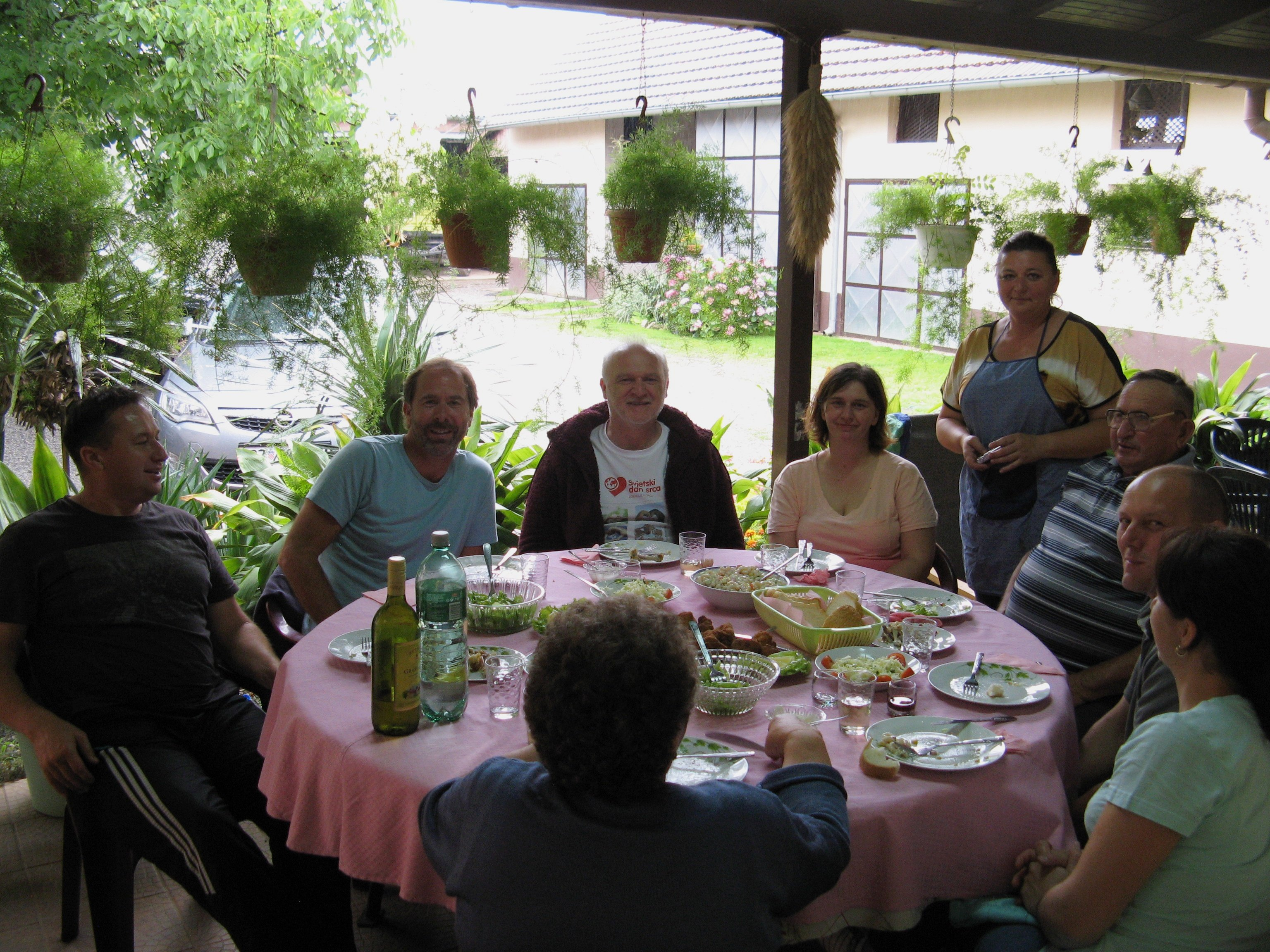 Group of people sitting around a dining table in Croatia enjoying a family farm-to-table dinner