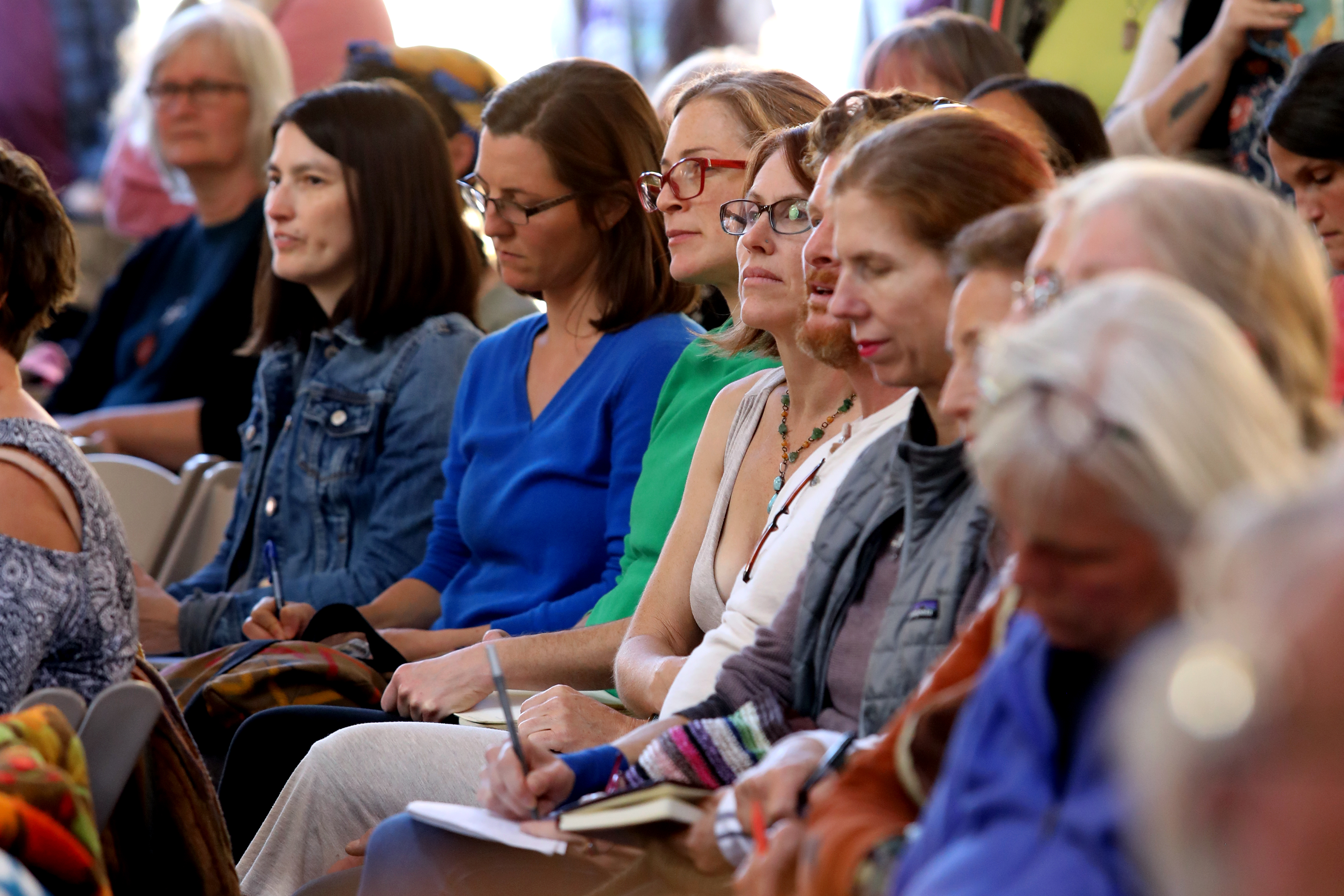 Group of people of mixed ages listening to a speech.