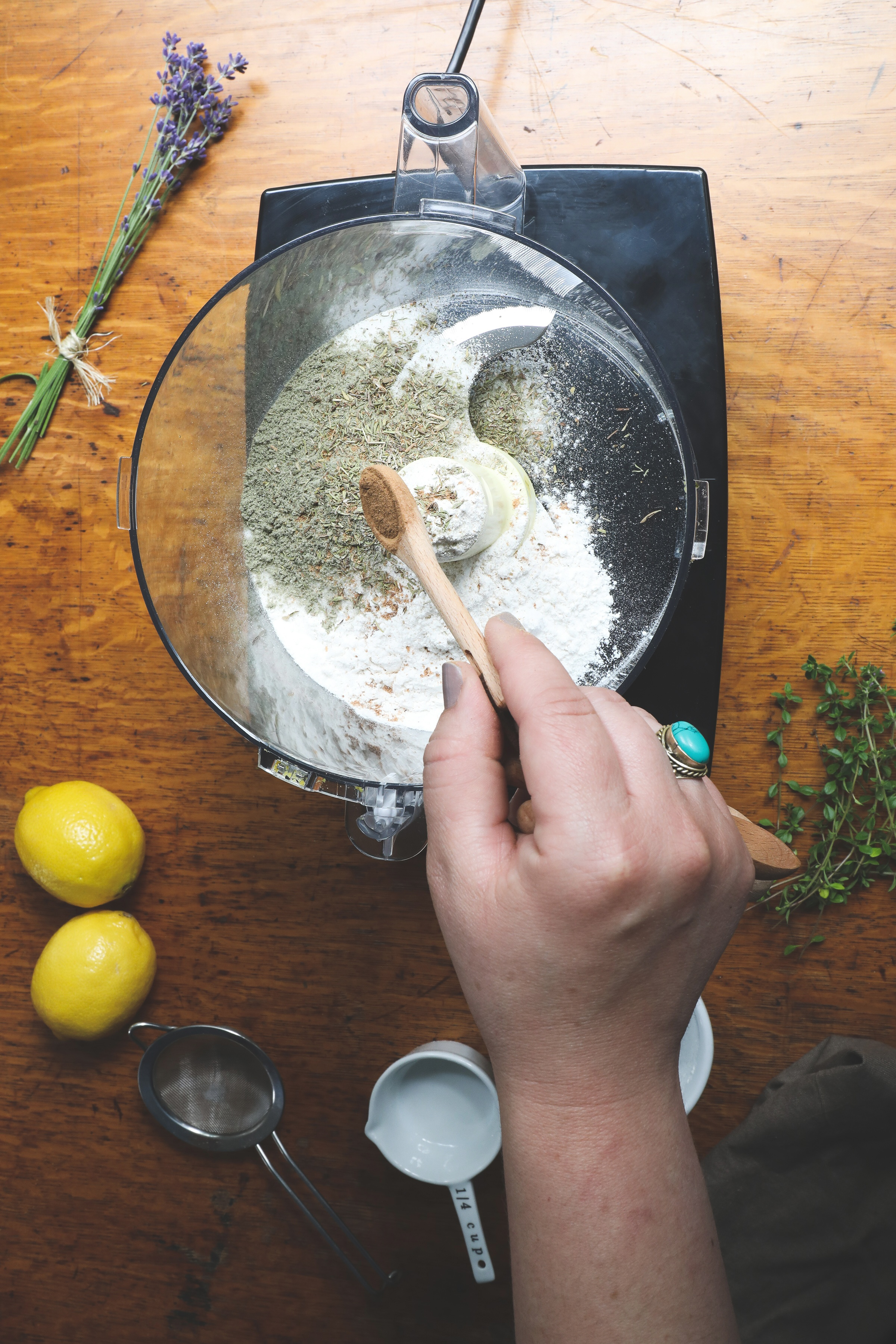 Hand adding spices to food processor with wooden spoon to make lemon bars