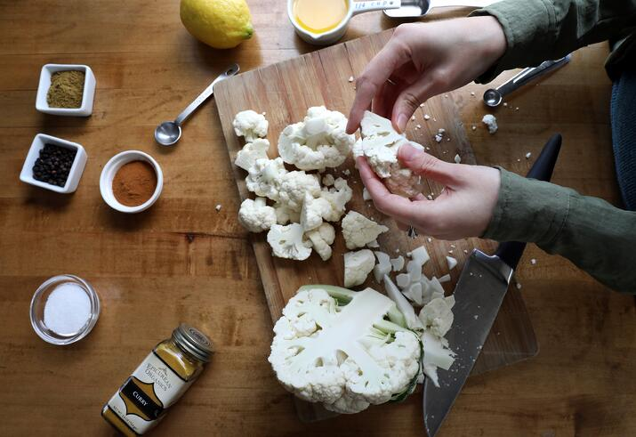 Hands breaking cauliflower into small pieces to make curry cauliflower