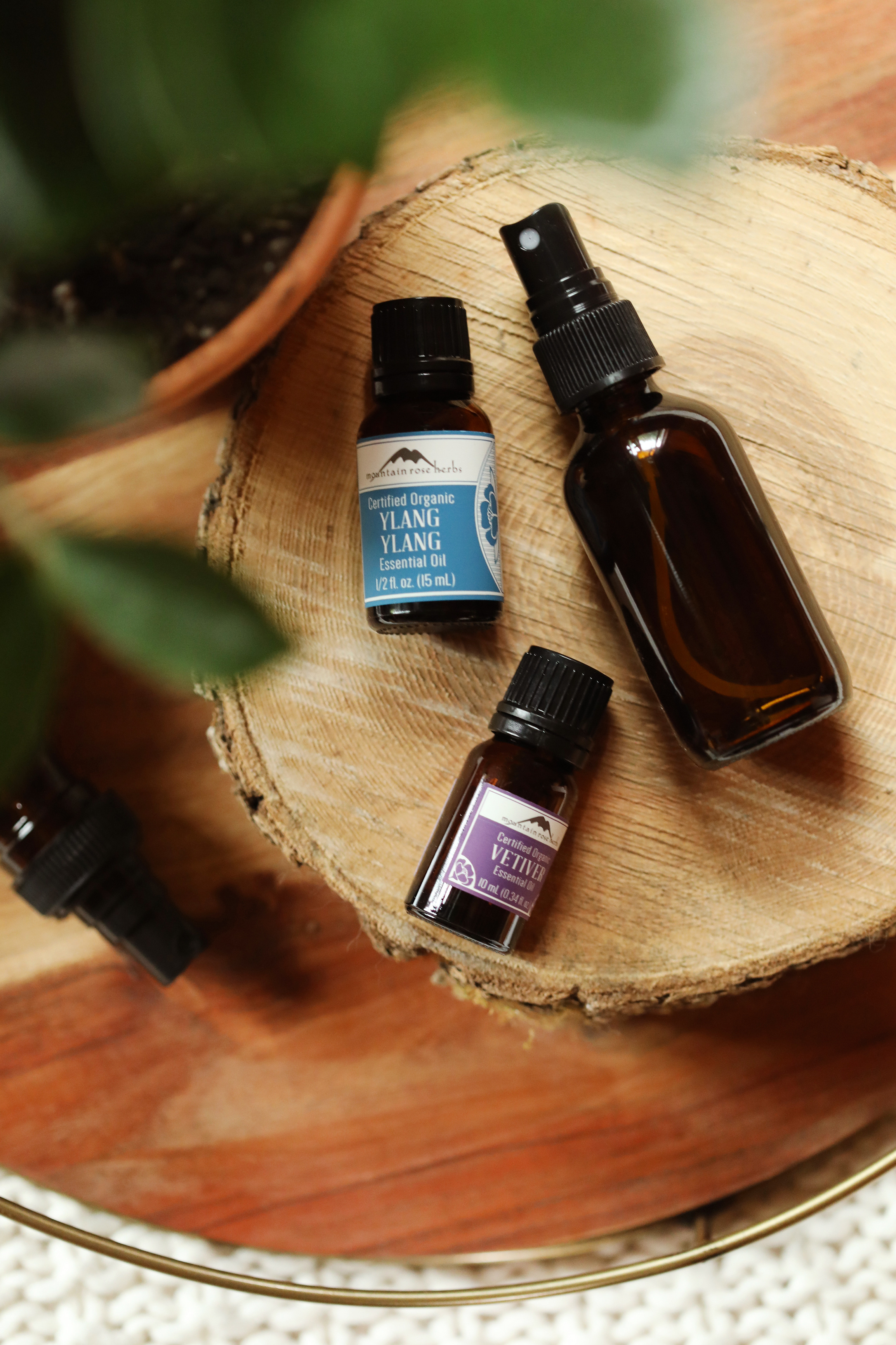 Bottles of organic essential oils from Mountain Rose Herbs on wooden round with glass spritzer bottle.