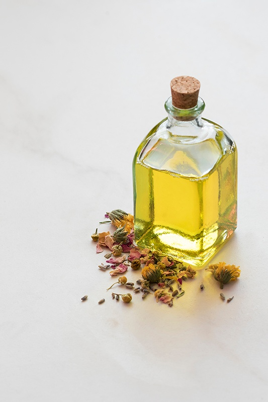 Massage oil in glass jar surrounded by organic rose petals, calendula flowers, and chamomile