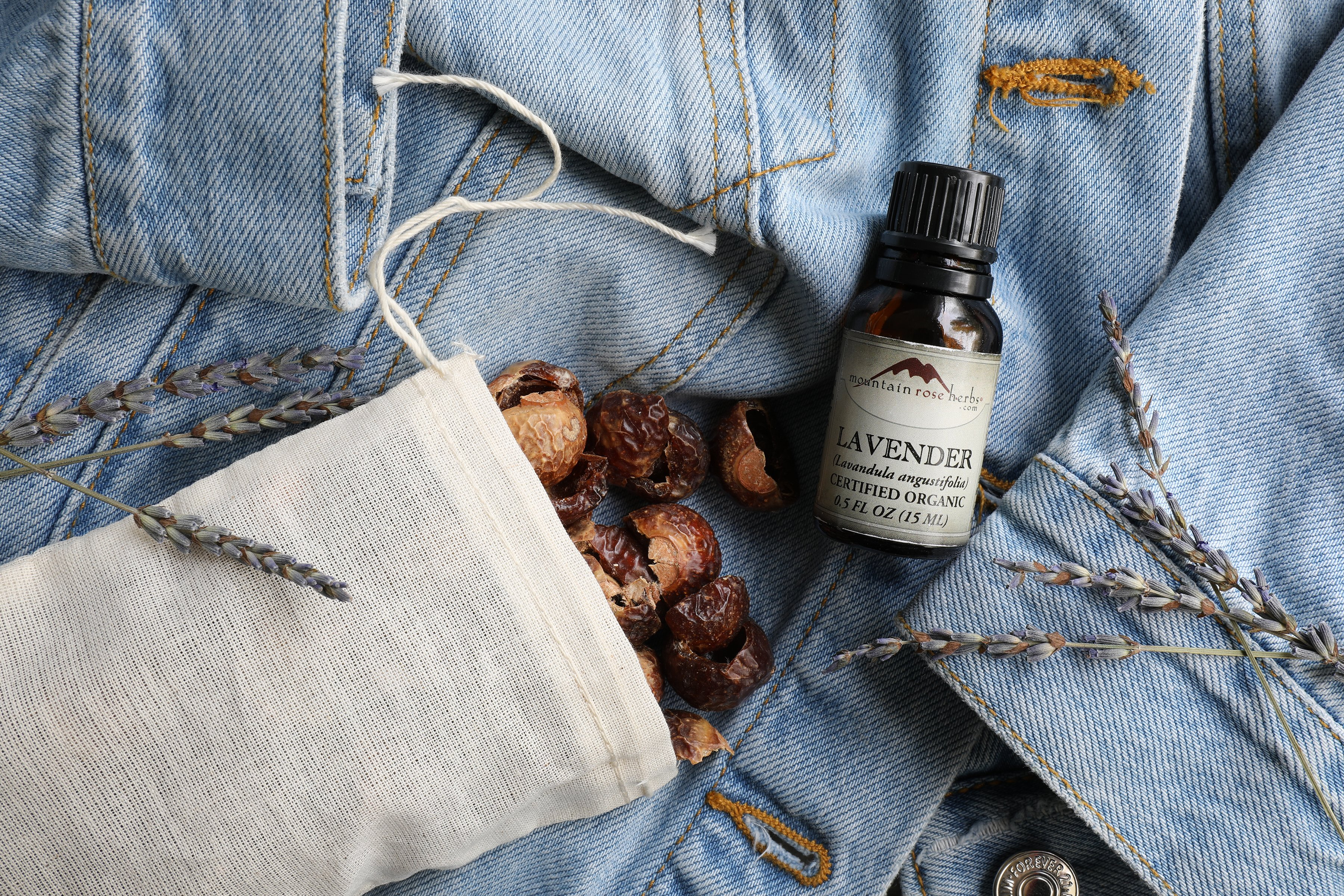 Bag of soap nuts spilling out of cotton bag with bottle of essential oil sitting on denim fabric.