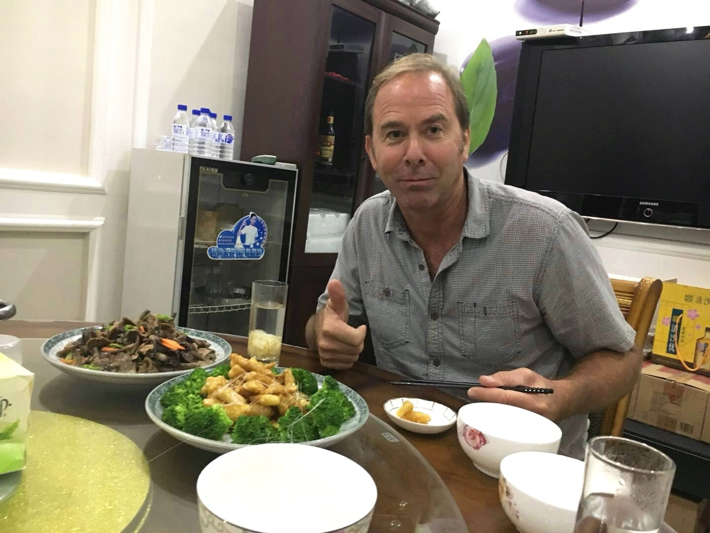 David enjoying multi-course traditional Chinese meal in Chinese processing facility office.