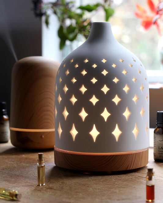 Two ultrasonic water diffusers for essential oil diffusing at home. Serene House light house and supernova essential oil diffusers with small essential oil vials.