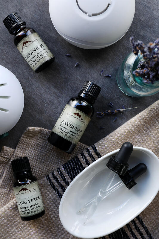 Bottles of organic essential oils and fresh herbs on a fresh colored linen cloth placed on a grey wooden table.