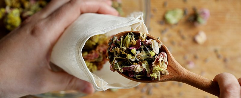Filling a cotton muslin bag with herbal ingredients for a diy dream pillow to aid in restful sleep. Hops flowers, rose buds, helichrysum and chamomile flowers lend a soothing aroma throughout the night.