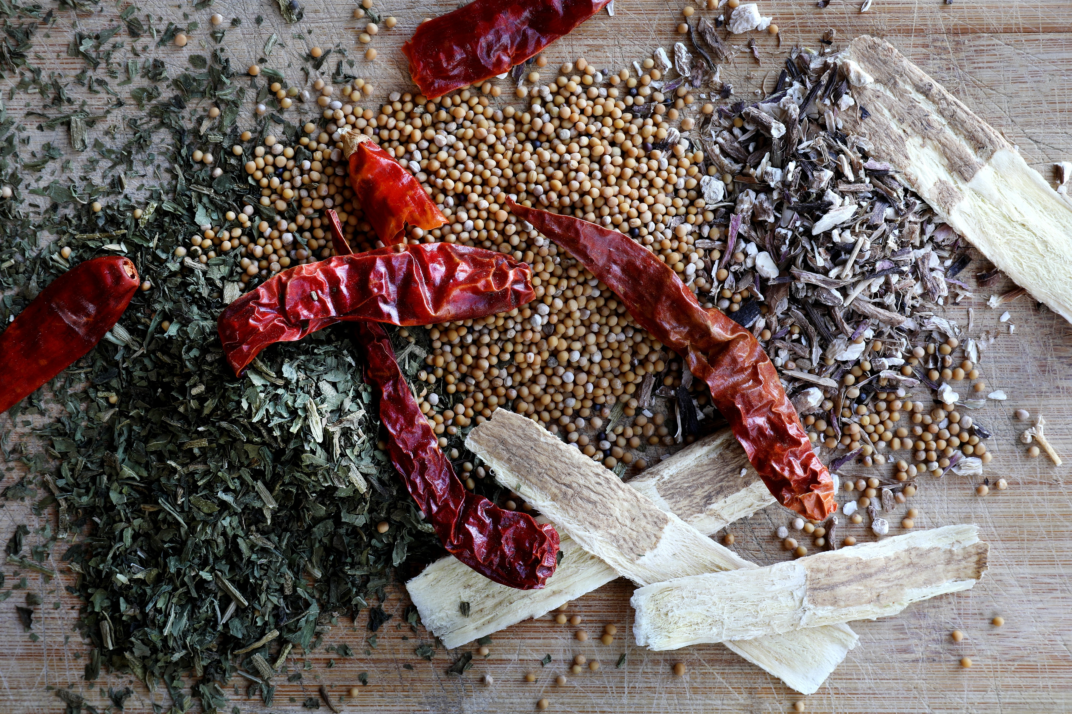 Vibrant colorful herbs, spices, and barks displayed on wood