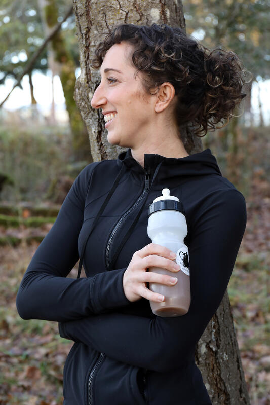 Fit young woman leaning against a tree in an outdoor setting holding a sporty water bottle.