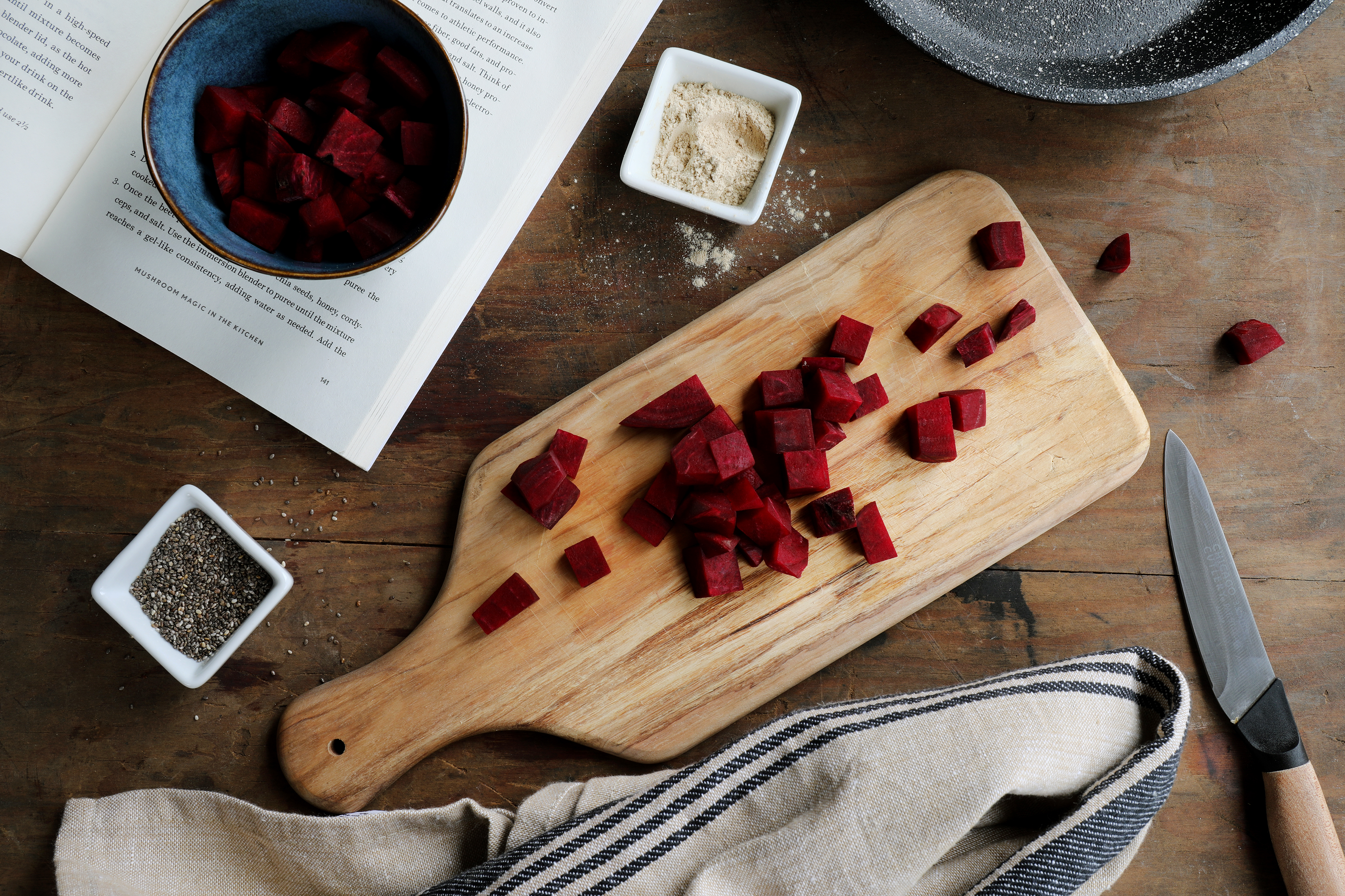 Cutting board with chopped beets with small bowls filled with other botanical ingredients.