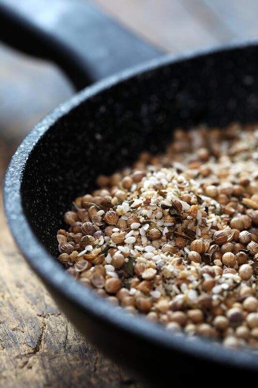 Dukkah seed and nut sprinkle lightly toasted in cast iron skillet.