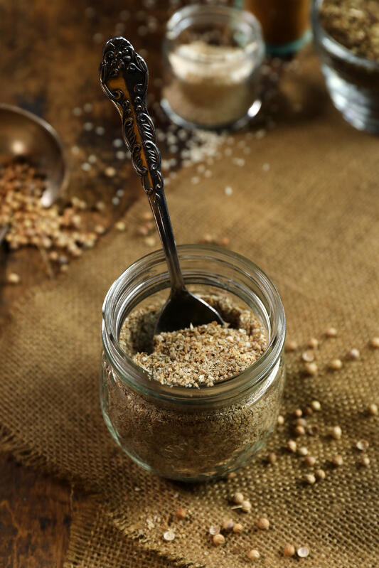 Dukkah spice nut and seed blend in glass jar with spoon.