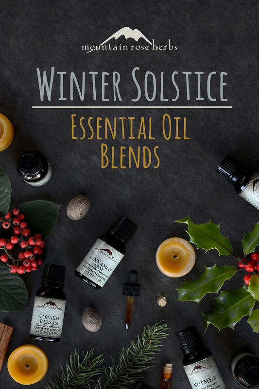 Various holiday themes are assembled with essential oils used to create holiday aromas for your home diffuser. Cinnamon leaf essential oil, copaiba balsam essential oil, and nutmeg essential oil arranged with beeswax tea lights and holly.