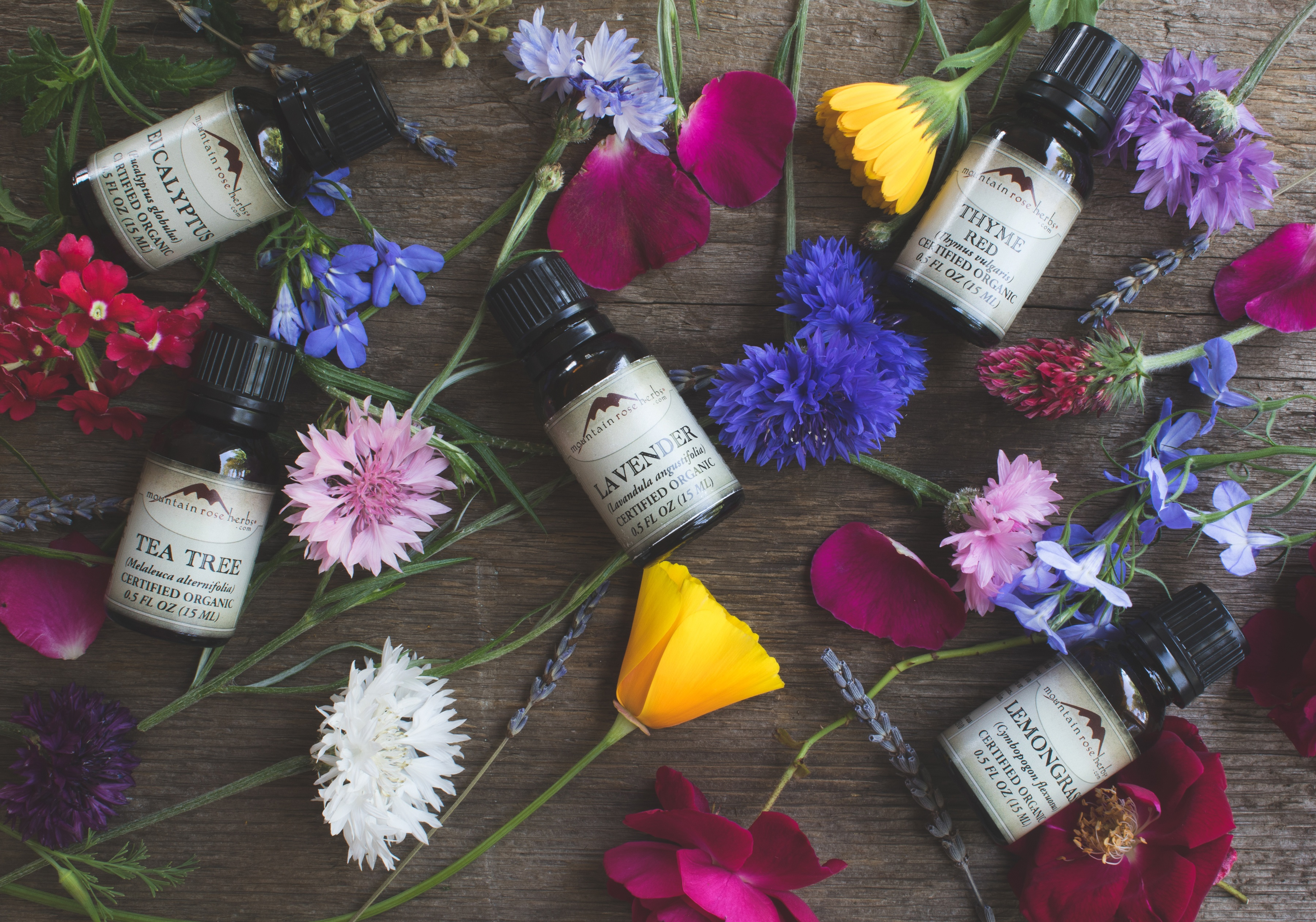1/2 oz. bottles of essential oil laying out on wooden surface with flower