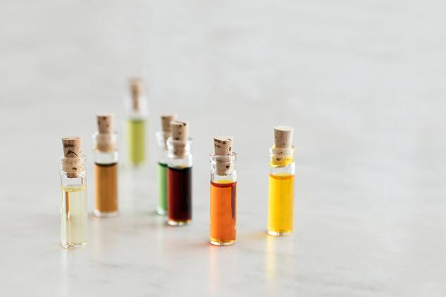tiny cork top glass vials filled with different colored essential oils sitting on marble table