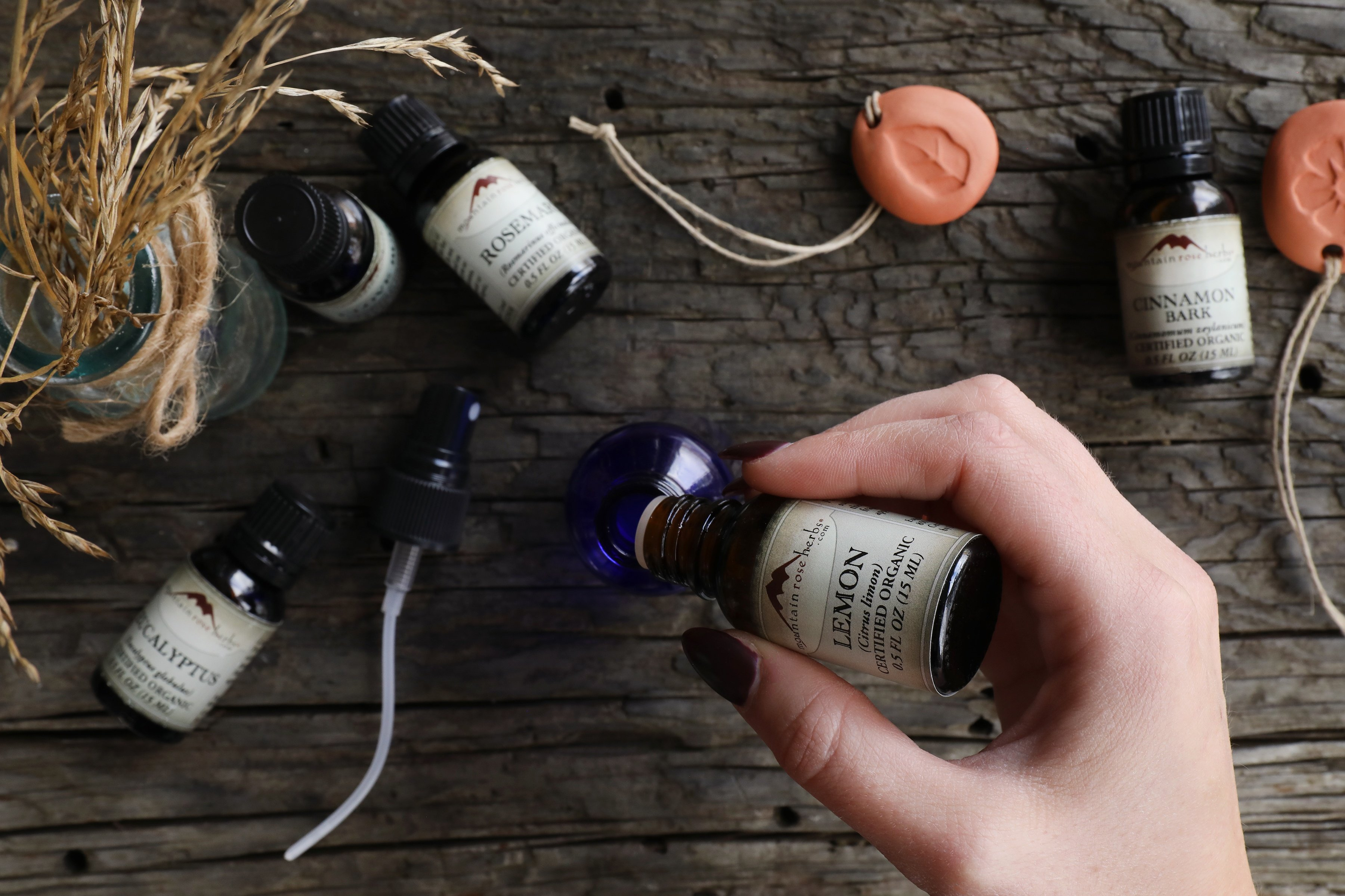 Hand pouring essential oil into cobalt glass bottle with other essential oils displayed on rustic wood.