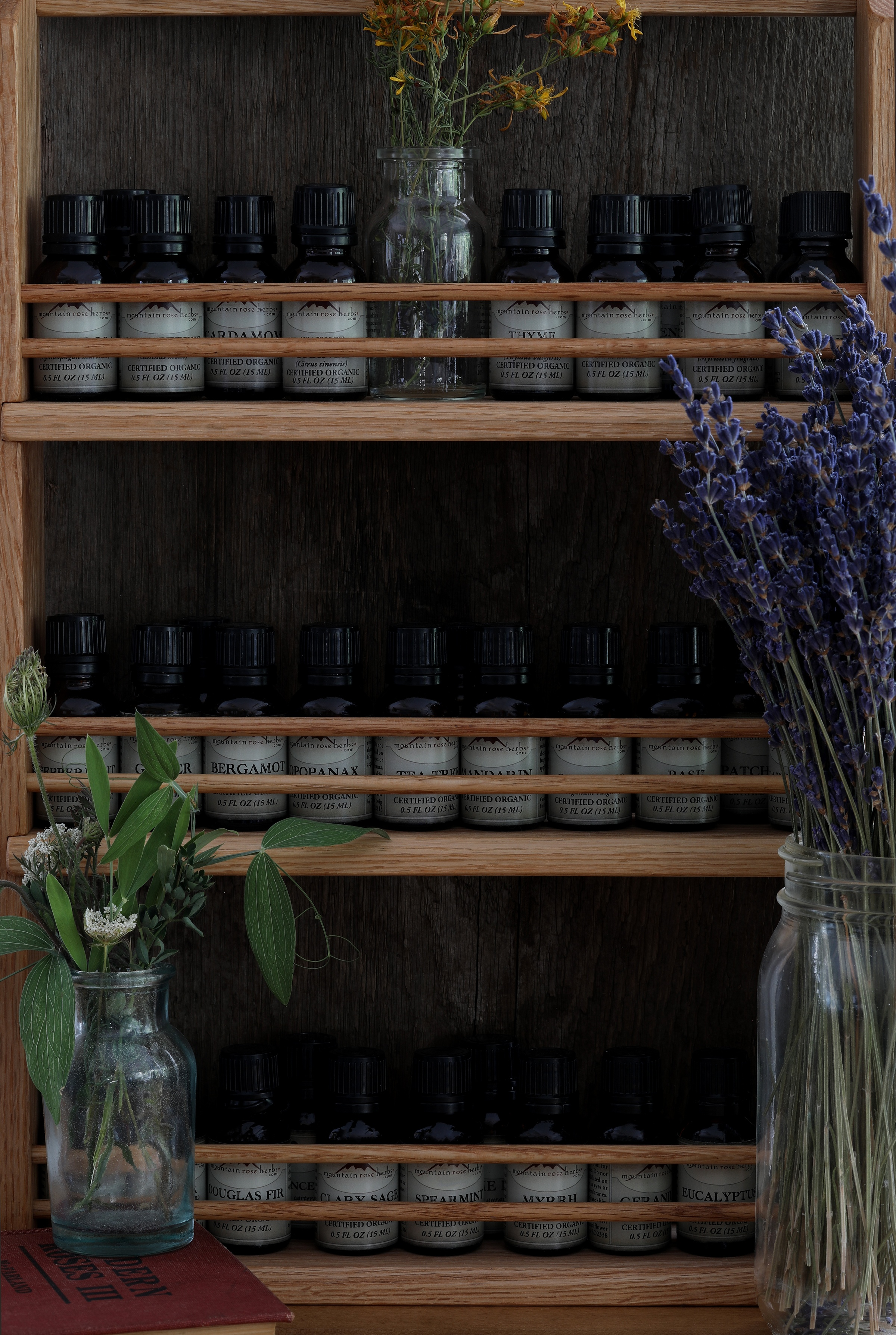 Essential oils stored on a wooden shelf in bottles indoors surrounded by dried herbs in mason jars