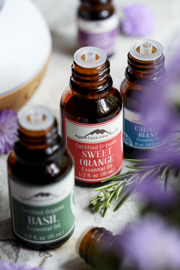 Bottles of Mountain Rose Herbs' essential oils that can be supportive with stress management, including basil, sweet orange, and calming blend.